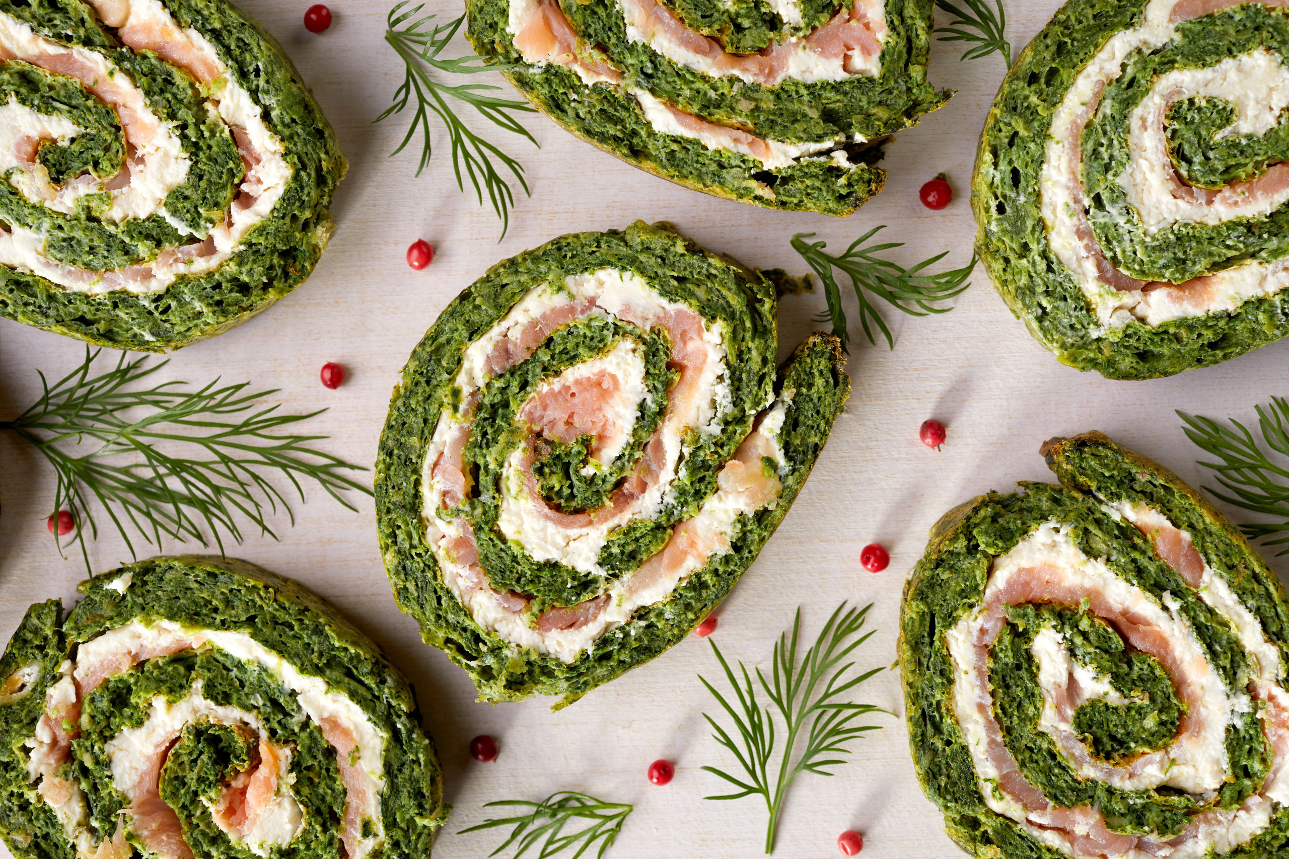 Spinach roulade stuffed with cream cheese and smoked salmon sliced on a white background